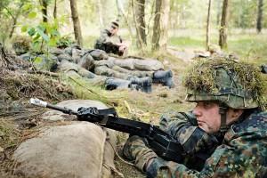 Ein Soldat liegt gelangweilt in seiner Schuetzenstellung.
